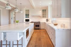A trio of white industrial pendants illuminate a white kitchen island topped with calcutta marble lined with modern white counter stools.