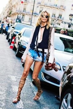 Anja Rubik wears a low cut blouse, vest, skinny scarf, belted cutoffs, lace-up sandals, round sunglasses, and a knit bag