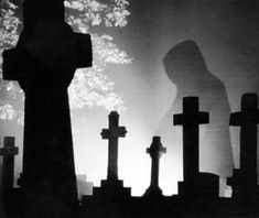 """This monk ghost photo was taken in 1990 by Derek Stafford who visited St. Mary's Church in Prestbury, Gloucestershire.  He was apparently taking photos of back-lit gravestones when the anomaly was unknowingly recorded in one of his pictures.    Locals believe it is the legendary """"Black Abbot"""" ghost that walks the churchyard at night."""