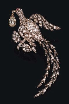 19th Century bird of paradise brooch, pavé-set with old mine and rose-cut diamonds, with trailing diamond-set tail, with a diamond briolette dangling from its beak, perched on an old mine and rose-cut diamond branch with leaves.