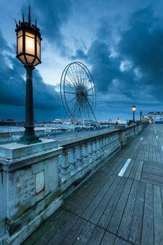 Anoitecer no pier Brighton, em Londres, Inglaterra, Reino Unido. Ao fundo se vê a  London Eye, também conhecida como Millennium Wheel (Roda do Milênio). Fotografia: Slawek.