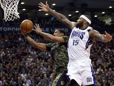 Toronto Raptors forward DeMar DeRozan (10) makes a basket past Sacramento Kings forward DeMarcus Cousins (15) during the first half of an NBA basketball game Wednesday, Jan. 28, 2015, in Toronto. (AP Photo/The Canadian Press, Nathan Denette)