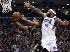Toronto Raptors forward DeMar DeRozan (10) makes a basket past Sacramento Kings forward DeMarcus Cousins (15) during the first half of an NBA basketball game Wednesday, Jan. 28, 2015, in Toronto. (AP Photo/The Canadian Press, Nathan Denette)