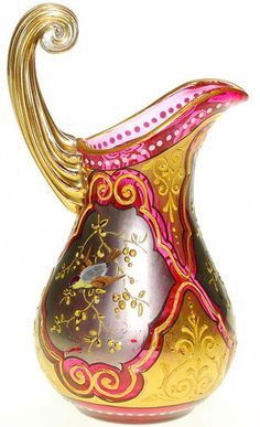 A  Moser glass cranberry creamewr with fired on silver and gold windows, a bird or raised branches in each. Gold highlights a unique clear reed scroll handle. Czechoslovakia, circa 1850-1900