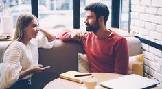 Young woman and man talking during first date in cozy coffee shop enjoying free time together,hipster girl checking notification on mobile while spending time with boyfriend having lovely conversation