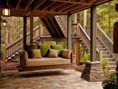 The downstairs patio features a hanging bed furnished with plush cushions in green and earth tones to complement the wooded scenery.