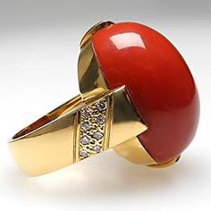 This magnificent vintage natural red coral cabochon cocktail ring is crafted of solid 18k yellow gold and features high quality natural diamond accents.