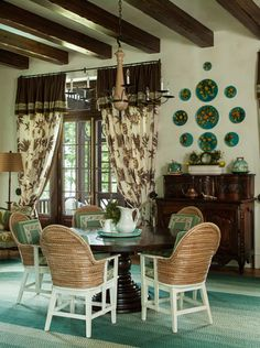 A walnut pedestal table is unexpectedly paired with reed-backed Orkney chairs in the hearth room. The hand-braided rug was custom crafted in Pennsylvania. Majolica plates featuring citrus fruits tie the room to the rest of the house's theme. Interiors by Florida design firm Taylor & Taylor