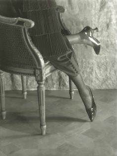 c.1919 Baron de Meyer. View of model's legs, kneeling on a chair in the Empire style, wearing black patent leather shoes with colored tips and heels, by Slater