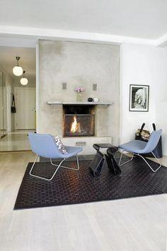 VARMT SAMLINGSPUNKT:  Om vinteren brukes peisen flittig, og gir b�de varme og god stemning. Stolene Ray Lounge Chair fra Hay. Bordet og gulvteppet Moose Mat er fra Illums.