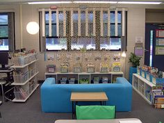 "BEAUTIFUL Classroom Library (slip covers for sofas in light blues & greens, light wood, globe lighting - IKEA).  Hanging ""divider""."