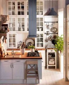Ikea: I have loved this kitchen since i first saw it. tiny, butcher block counter, to the ceiling glass cabinets and tons of natural light