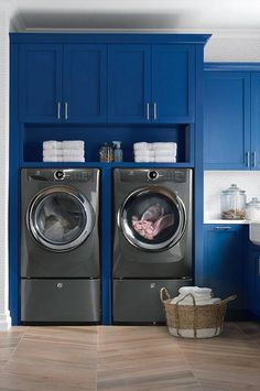 Contemporary blue and white laundry room boasts a recessed Electrolux washer and dryer sat on Soleras Avana Chevron…