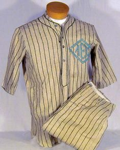 This is an exceptional 1910-20's Spalding Baseball Uniform. This vintage baseball relic is a matching jersey and pants in an unusual color combination. The material is a light tan wool with dark green pin striping. A lighter green felt emblem is sewn onto the left chest. Made of the highest quality, the pullover jersey features the Spalding cloth patch and the same patch is also found in the pants.