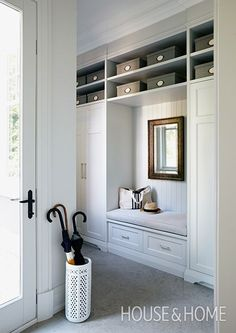 In this mudroom by designer Brian Gluckstein, a wall of built-in storage with open shelving and twin closets keeps clutter at bay. | Photographer: Michael Graydon