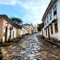 """Tiradentes é uma cidade muito charmosa, com o centro histórico preservado, com inúmeras lojinhas de artesanato e cafés. As ruas foram feiras com pedras grandes e que não se encaixam umas às outras, conhecidas como """"solteironas"""". #minasgerais #tiradentes #viagemjovem Road Maps, The Streets, Fair Grounds, City, Craft, Destinations, Centre"""