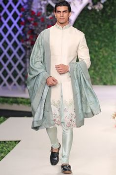 Featuring an ivory floral embroidered motif sherwani based in matka silk. It comes with a solid monga silk kurta and printed spun silk churidaar. It is paired with a printed stole in spun silk accented with embroidered border. Fabric: Matka silk, Spun silk, Monga silk Care Instructions: Dryclean only.