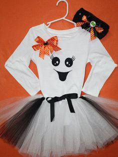 Your little one can be a friendly ghost in this adorable outfit for Halloween.  White long sleeve top for girls and long sleeve bodysuit for baby girls embroidered and appliqued with a happy ghost face.  Set comes with a matching tutu in black and white, and a matching headband.  Perfect for a Halloween party or get together. This can be personalized.  If you would like it personalized just put your child's name in the notes on your order. I don't charge extra for personalization on outfits…