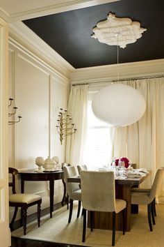 Chic dining room with black painted ceiling & ivory walls