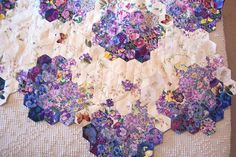 English paper pieced hexagons in floral prints for watercolor wash effect. The isolated little golden butterflies are a very nice touch, both for accent and for color.