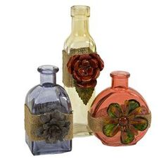 "Set of three glass bottles with burlap and blossom accents.       Product: Small, medium and large bottle    Construction Material: Glass, gunny bag and wrought iron     Color: MultiFeatures:   Elegant floral design   Will enhance any space    Dimensions: 5.5"" H x 3.25"" W x 2.5"" D (large)"