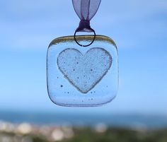 A handmade fused glass gift tag embossed with a heart, perfect for adding a special touch to your birthday gifts, hanging in a window or as a wedding favour!