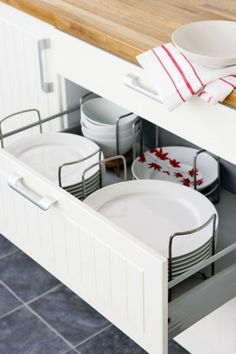 Dish drawers with pegs or moveable holders keep everything firmly in place, and can be shifted around to fit the exact dimensions of your plates. Ikea sells drawer dividers in various sizes.