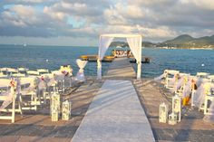 bamboo arch, with white fabric decorated with  touch of lavender , on the arch & on the chairs along the aisle , white lanterns  made by www.fee-des-caraibes.com Face book: Mariages À Saint Martin