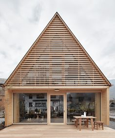 innauer matt adds pitched timber extension to gardening shop in austria