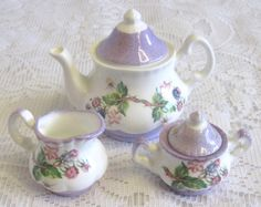 What a cute little set this is, whether you are a miniatue collector, or want to have a tea party for your dolls! The teapot, lidded sugar bowl and cream jug were made by Raesuevic Ceramics in the 1970s and the company is no longer operational. The three items have been stamped Bone China Made in England and additionally the teapot has the companys backstamp and Hand Decorated.  The beautifully scalloped set has been hand painted with blackberry branches, berries and flowers on both sides…