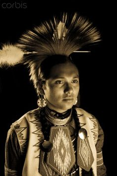 Sepia/gold tone technique of a Native American teenage boy dressed in traditional pow wow regalia and roach headdress with black background. Fort Hall, Idaho, USA. Marilyn Angel Wynn photography