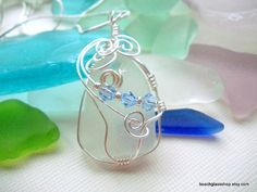 A perfect piece of frosted white beach glass, measuring 1 7/8 in length and embellished with pale blue swarovski crystals! This stunning beach glass pendant has been wrapped in non tarnish artistic wire, and the swirls certainly make it one of a kind! An 18 sterling silver filled necklace is included in this purchase.    Enjoy this piece of history from the shores of Lake Erie!      All of my beach glass is authentic and surf tumbled, found on the shores of Lake Erie.    Each piece will ...