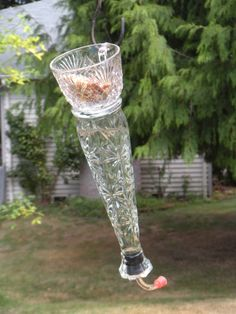 Vintage cup acts a the hook for this repurposed glass vase turned hummingbird feeder.  Cup also holds bird seed or can be a bird bath!