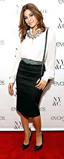 Eva Mendes celebrated the Sept. 18 launch of her new clothing line in NYC wearing a white blouse bodysuit and black pencil skirt from her collection. Her shoes and bag are by Saint Laurent.