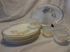 "This set would have been used for snack times - coffee and slice of coffee cake, tea time, or just straight up dessert service with a tasty beverage on the side.  This set is in great shape, save one chipped plate (pictured). Otherwise, these are in great vintage condition. Milk glass decorated and rimmed in 22K gold.  Plate measures 10.25"" long x 7"" wide. Cup measures 2.5"" tall x 3.75"" wide."