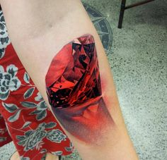 Realistic red jewel tattoo on arm. Holy cow, that's amazing!!