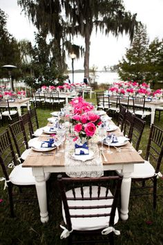 So beautiful - outdoor setting with wooden tables & chairs, bright pink floral, gold table runners & navy bows