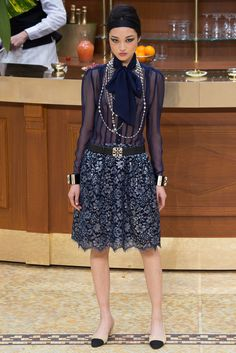 This look is by Chanel - Fall 2015. This blouse looks very similar to that which would have been paired with a suit in the early 1930s. This is seen with the tie into a bow around the neck line.
