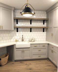 Farmers sink, white tile, wood shelves, stain of floor, wicker baskets