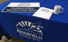 Branded table cover, sign, folder and mug for Ridgefield School District. #VisualIdentity is important in expressing the culture and the experience you're involved in.   #Design #Marketing #Branding #Print #VanWA #RidgefieldWA #ClarkCoWA