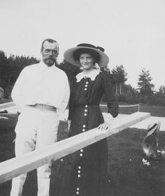 Nicholas and Tatiana, with Anastasia sitting on the grass