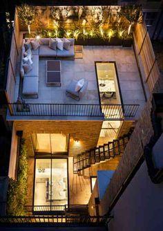 Une maison en ville avec une terrasse sur le toit