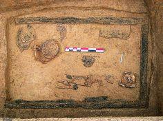 Inhumation d'une jeune adolescente dans une chambre funéraire sous un tumulus, VIe-VIIe s., Hégenheim (Haut-Rhin), 2004.  Les dimensions de la tombe, la richesse du mobilier funéraire et les offrandes alimentaires sont des marques d'un statut social élevé.