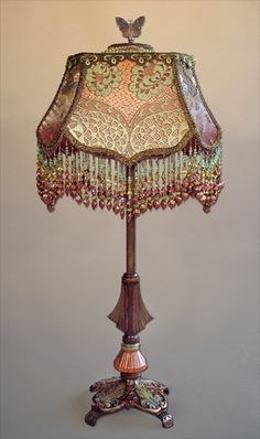 Stylized vintage deco lamp base with Royal Loop shade with a slightly asian feel. The shade is hand dyed a copper/persimmon color and covered in antique green silk lace, the narrow panels are covered in embroidered net. The top panel is covered with old floral appliqués covered with metallic mesh. Multicolored hand beaded fringe adorned with swarovski crystals.