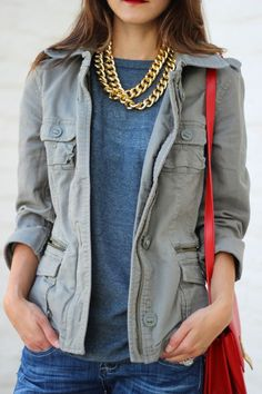 Grey jacket, blue shirt, gold necklace, red cross-body bag