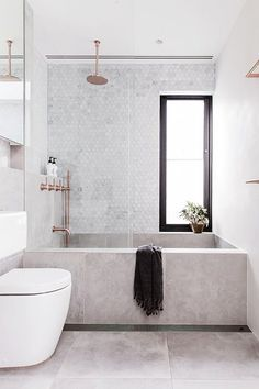 Don't let anyone tell you that concrete can't be ultra glam and luxurious. This bathroom's concrete base paired with lovely copper accents and a black-trimmed window is just about as luxe as bathrooms come. Read more at: https://nyde.co.uk/blog/springs-concrete-trend/