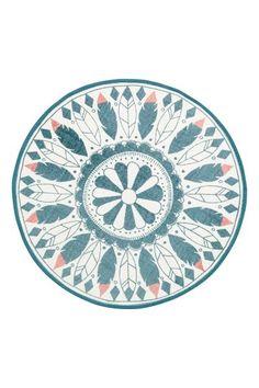 Okrągły dywanik z bawełnianej tkaniny we wzorzyste nadruki na wierzchu. Brzeg obszyty tasiemką.