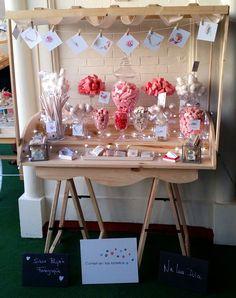 Carrito de dulces, con tonos rosas para la fiesta de Malas madres, repleto de dulces como galletas, cakepops, nubes, gominolas, bombones...