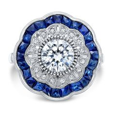 This stunning new vintage piece is set with a beautiful, natural blue sapphire and diamond double halo. Calibre cut sapphires accent a clean bezel set center diamond. Sparkling shank and intricate gallery complete this exquisite piece. Center Stone: Diamond Weight: 1.00 ct. Color: G Clarity: SI1 Shape: Round Side Stones: Sapphire Weight: 1.35 ct. Color: Blue Clarity: VS Shape: Calibre Cut Side Stones: Diamond Weight: 0.20 ct. Color: G Clarity: VS Shape: Round