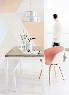 Light pink dining room hues and a grapefruit color inspired armchair.